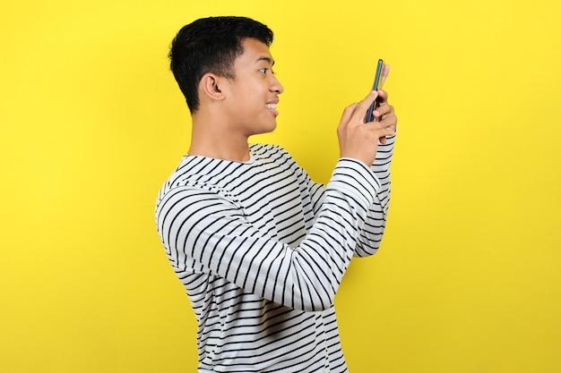 Heureux jeune homme asiatique souriant à l'aide de smartphone isolé sur fond jaune
