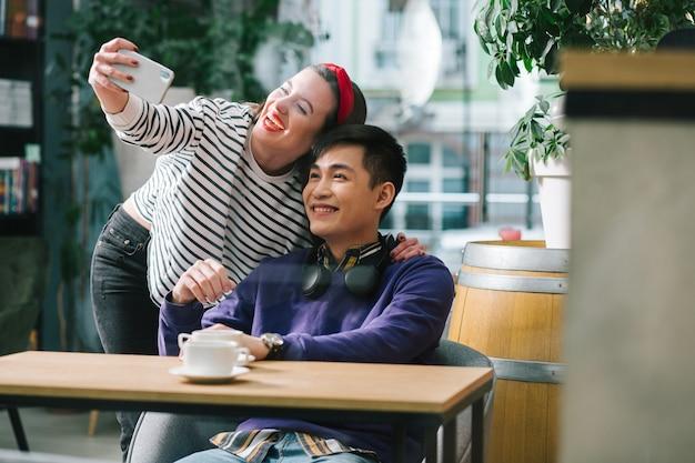 Heureux jeune homme assis dans un café avec une tasse de café et sa jolie petite amie joyeuse prenant un selfie avec lui