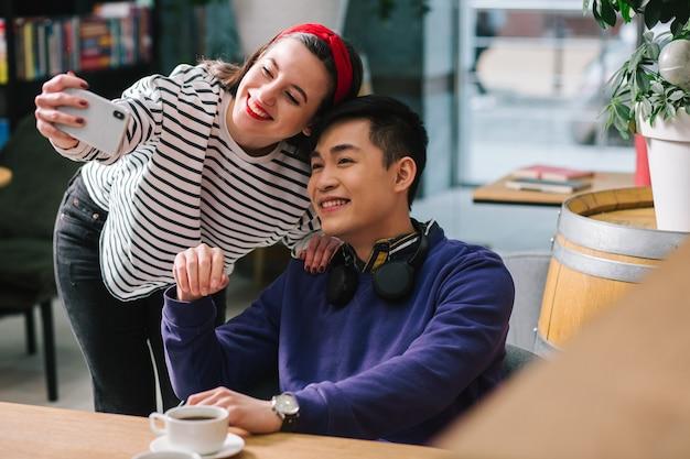 Heureux jeune homme assis à la table avec une tasse de café et une dame souriante se penchant vers lui avec un smartphone et prenant des selfies