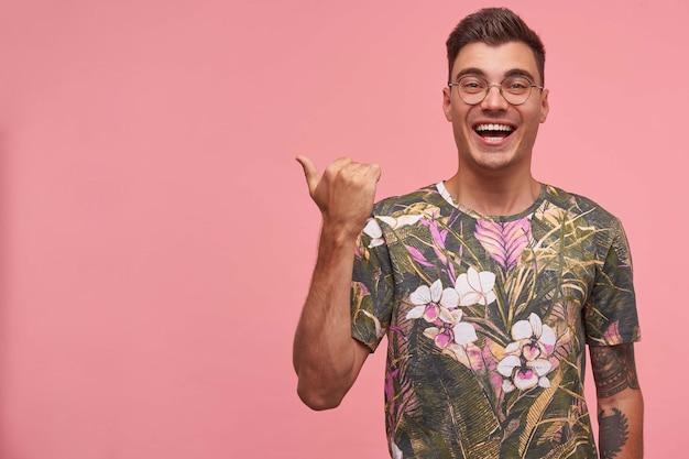 Heureux jeune homme attrayant avec des lunettes pointant avec le pouce de côté, regardant directement et souriant joyeusement, debout