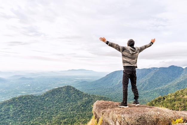 Heureux jeune homme au sommet de la montagne répandre la main et profiter de la vue sur la vallée vallée.