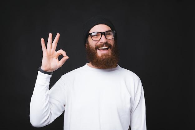 Heureux jeune homme à barbe portant des lunettes et montrant le signe ok