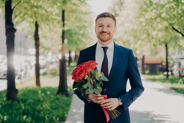 Heureux jeune homme avec une barbe soignée dans un élégant costume bleu foncé formel marchant joyeusement le long d'une ruelle verte dans un parc avec un beau bouquet de roses rouges dans ses mains par une journée ensoleillée pour rencontrer sa belle date