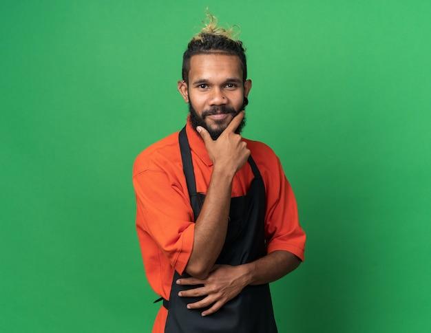 Heureux jeune homme barbier en uniforme gardant la main sur le menton regardant à l'avant isolé sur mur vert avec espace de copie