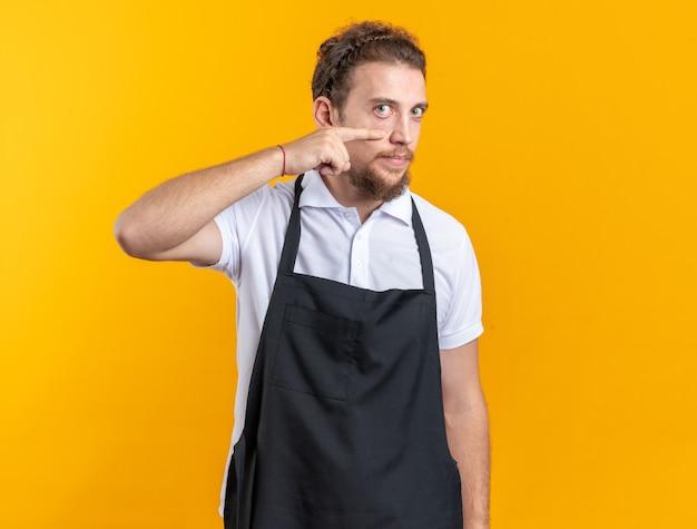 Heureux jeune homme barbier en uniforme tirant sur la paupière avec un doigt isolé sur un mur jaune