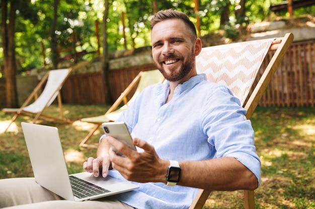 Heureux jeune homme barbu à l'extérieur à l'aide d'un ordinateur portable et d'un téléphone portable.