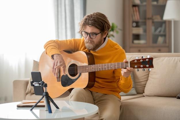 Heureux jeune homme barbu à lunettes, jeans et cavalier à la recherche de l'appareil photo du smartphone pendant le cours en ligne de jeu de guitare