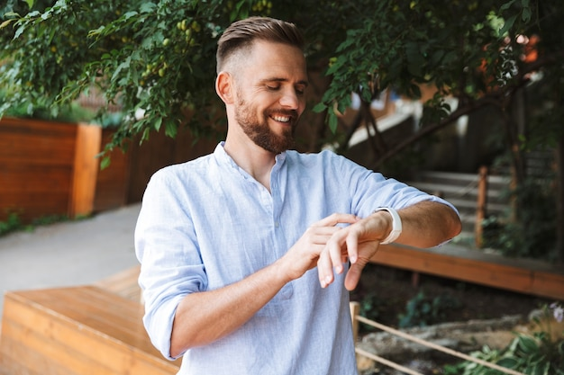 Heureux jeune homme barbu en regardant sa montre.
