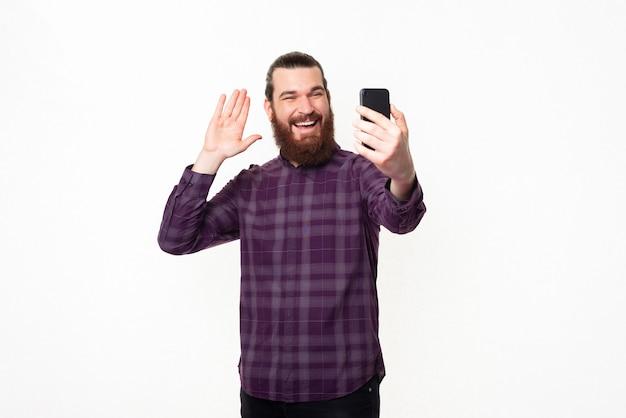 Heureux jeune homme barbu souriant, parler à quelqu'un avec smartphone et saluer