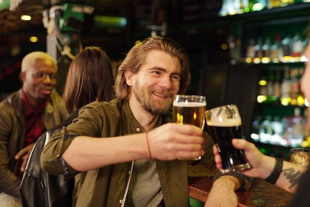 Heureux jeune homme barbu en tenue décontractée regardant son ami tout en trinquant avec des verres de bière devant la caméra et en parlant
