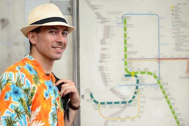 Heureux jeune homme beau touriste avec sac à dos à la carte d'itinéraire dans la gare