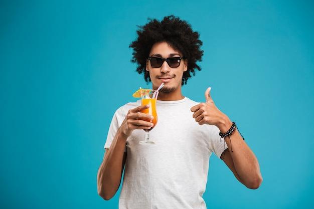 Heureux jeune homme bouclé africain buvant un cocktail montrant les pouces vers le haut.