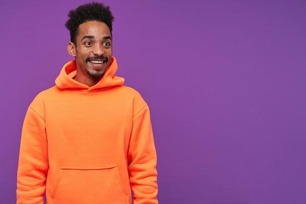 Heureux jeune homme brune à la peau sombre mignonne avec barbe étant agréablement surpris et se réjouissant avec un large sourire, vêtu de vêtements décontractés tout en posant sur violet