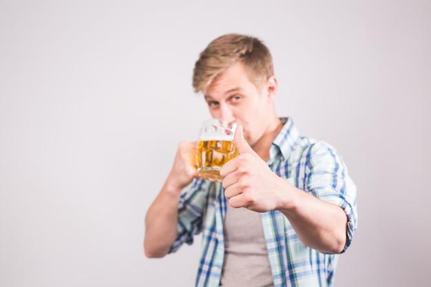 Heureux jeune homme buvant une chope de bière et montrant les pouces vers le haut