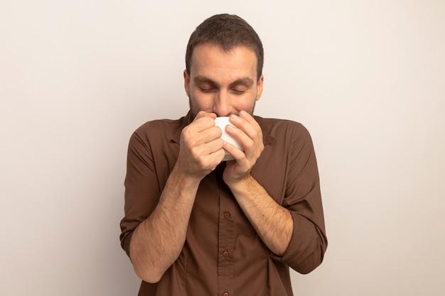 Heureux jeune homme caucasien, boire une tasse de thé avec les yeux fermés isolé sur fond blanc avec copie espace