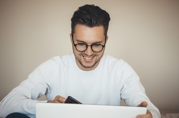 Heureux jeune homme caucasien avec des lunettes achète quelque chose en ligne pendant le verrouillage à l'aide de l'ordinateur portable et du mobile