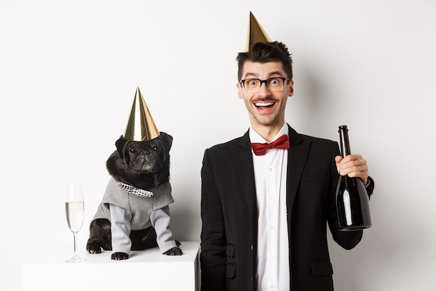Heureux jeune homme célébrant avec chien. carlin noir mignon et hipster portant des cônes de fête d'anniversaire, gars tenant du champagne, debout sur fond blanc.
