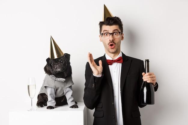 Heureux jeune homme célébrant des vacances avec un chien mignon, tenant du champagne et souriant