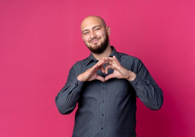 Heureux jeune homme de centre d'appels chauve faisant signe de coeur isolé sur fond cramoisi avec espace de copie