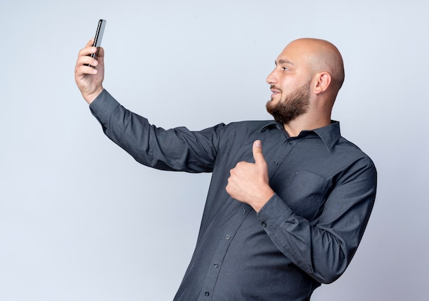 Heureux jeune homme de centre d'appels chauve montrant le pouce vers le haut et prenant selfie isolé sur fond blanc