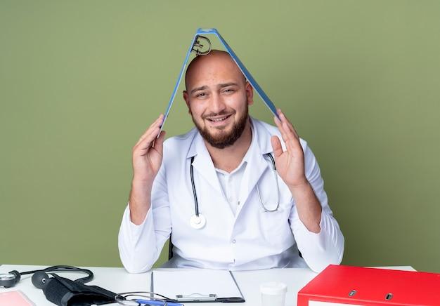Heureux jeune homme chauve portant une robe médicale et un stéthoscope assis au bureau