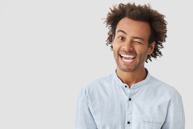 Heureux jeune homme clignote des yeux, a une expression positive, a les cheveux noirs croquants, habillé avec désinvolture