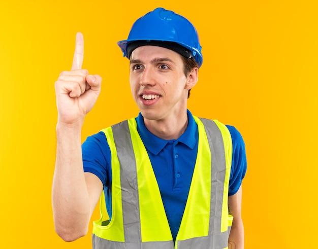 Heureux jeune homme constructeur en uniforme montrant un isolé sur mur jaune