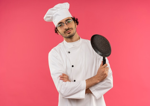Heureux jeune homme cuisinier portant l'uniforme de chef et des lunettes croisant les mains et tenant une poêle sur rose