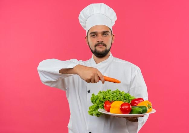 Heureux jeune homme cuisinier en uniforme de chef tenant la plaque de légumes et pointant avec la carotte à elle isolé sur l'espace rose