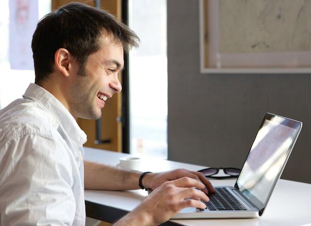 Heureux jeune homme dactylographie sur ordinateur portable