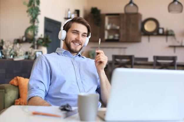 Heureux jeune homme dans les écouteurs travaillant à domicile pendant l'auto-isolement.