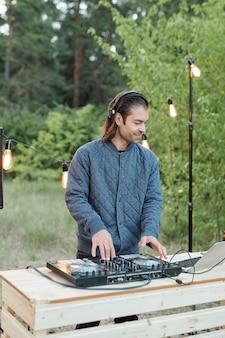 Heureux jeune homme dans les écouteurs et veste décontractée debout par table en bois avec carte stéréo et réglage du son contre les arbres verts