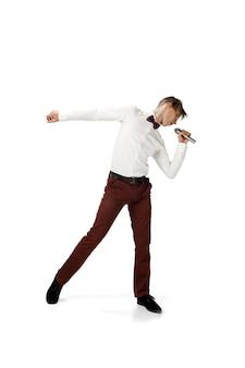 Heureux jeune homme dansant dans des vêtements décontractés ou en costume refaisant des mouvements légendaires de célébrité