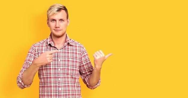 Heureux jeune homme debout avec le doigt pointé isolé sur mur jaune