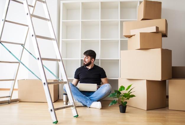 Heureux jeune homme déménageant dans une nouvelle maison