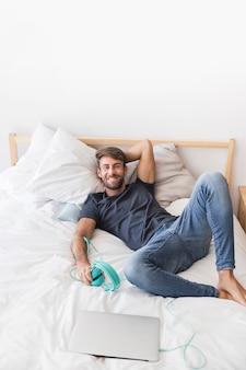 Heureux jeune homme écoutant de la musique sur le lit