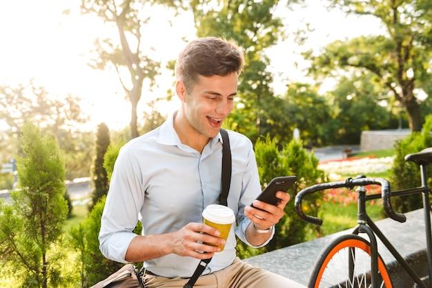 Heureux jeune homme élégant à l'aide de téléphone mobile
