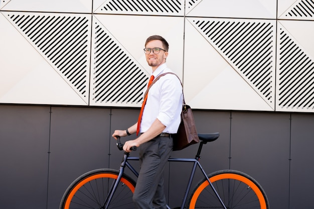 Heureux jeune homme élégant debout près du mur de l'architecture moderne tout en allant à vélo pour rentrer à la maison ou au café après la journée de travail