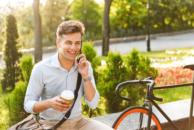 Heureux jeune homme élégant parlant au téléphone mobile
