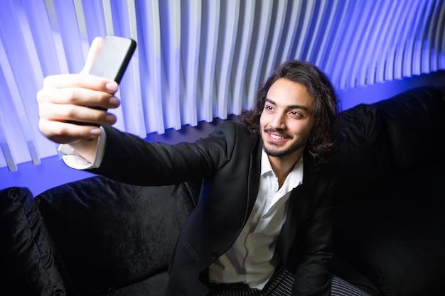 Heureux jeune homme élégant avec smartphone faisant selfie alors qu'il était assis sur un canapé en velours noir en boîte de nuit