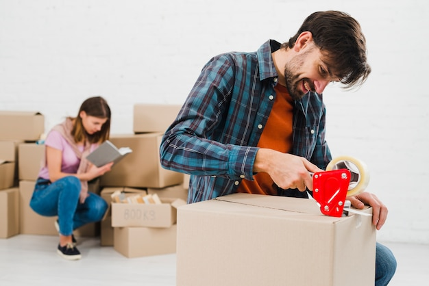 Heureux jeune homme emballant la boîte en carton et sa femme à l'arrière-plan
