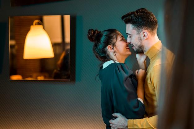 Heureux jeune homme embrassant une femme joyeuse dans la chambre