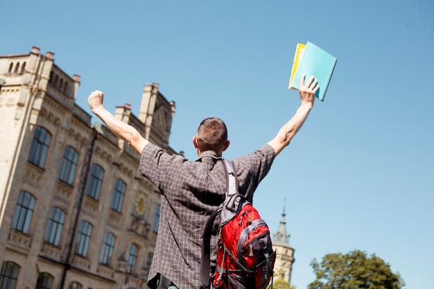 Heureux jeune homme étudiant leva les mains avec des livres en se réjouissant des résultats d'apprentissage.