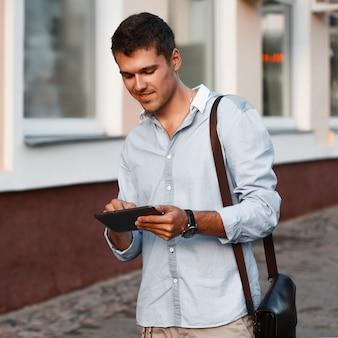 Heureux jeune homme exécutif à l'aide de tablette numérique