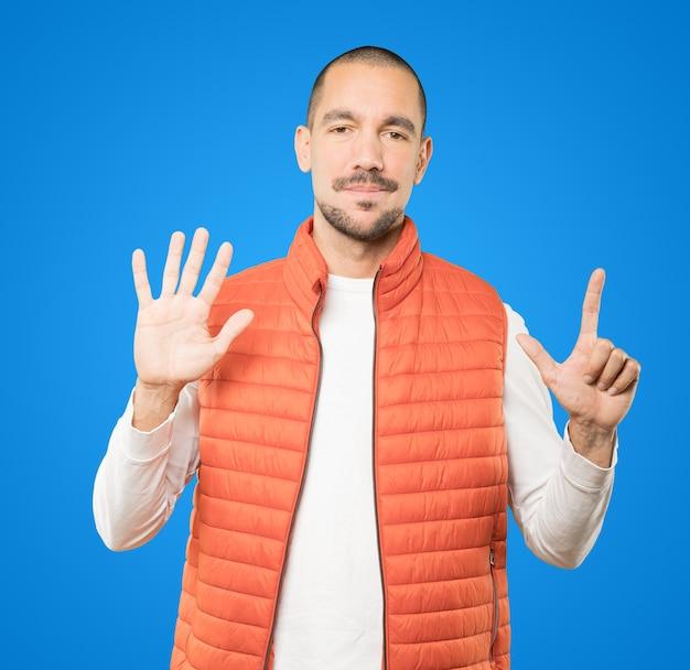 Heureux jeune homme faisant un geste numéro sept avec ses mains