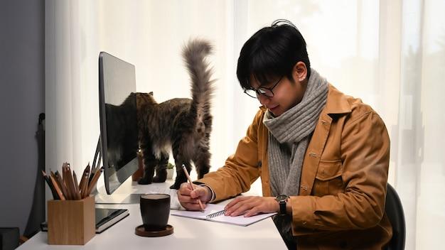 Heureux jeune homme faisant une note sur un ordinateur portable alors qu'il était assis dans une maison confortable avec son chat.