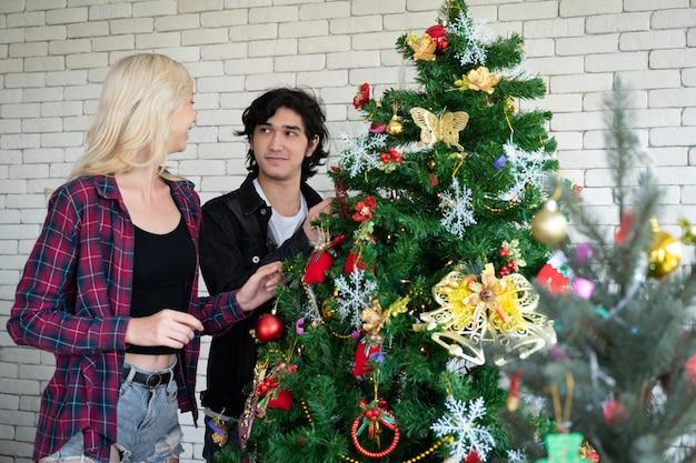 Heureux jeune homme et femme à la fête de noël, bel arbre et décorations.