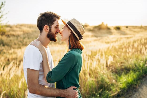 Heureux jeune homme et femme souriant et câlins en plein air au coucher du soleil.