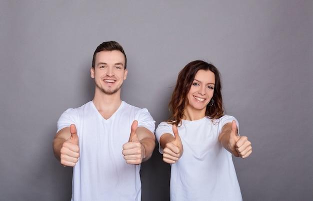Heureux jeune homme et femme souriante aux cheveux noirs en t-shirts blancs