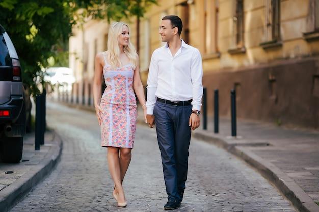 Heureux jeune homme et femme souriante marchant dans les rues de la vieille ville